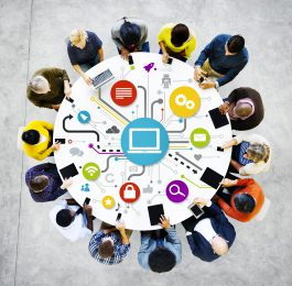 A group of fourteen people with different ethnic backgrounds sitting around a round, white table with different color social networking related icons on its surface.  There is a gray and white floor beneath them.